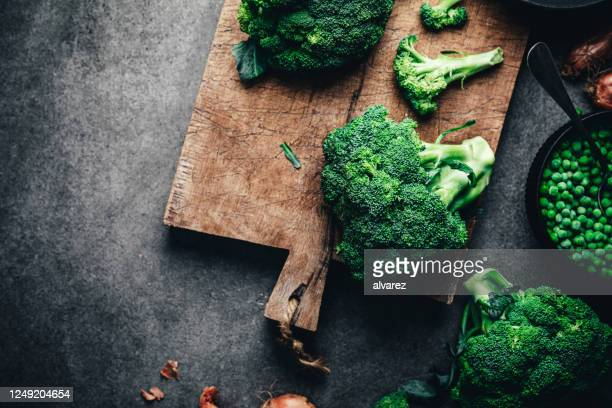 brócolis fresco na tábua de cortar - crucíferas - fotografias e filmes do acervo