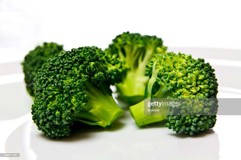 fresh brokkoli florets on white plate : Stock Photo