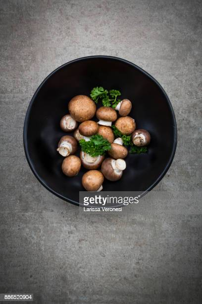 Fresh brown mushrooms and parsley in a bowl