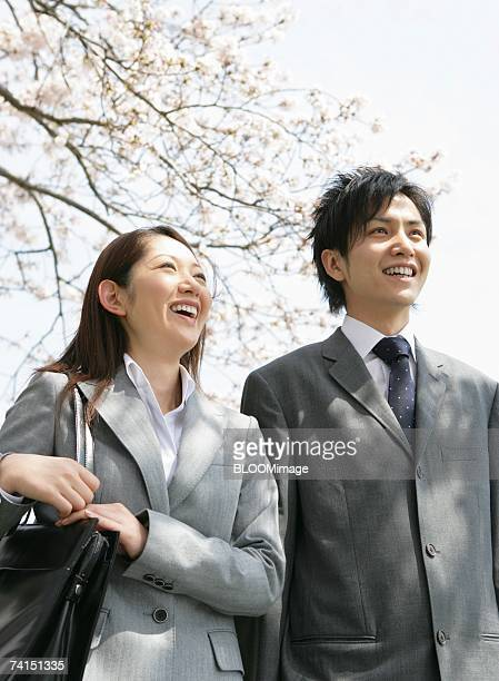 Fresh business couple standing with smiling under cherry tree