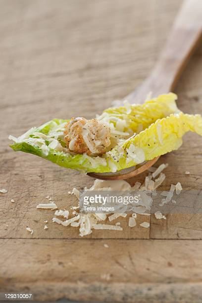 Fresh caesar salad on wooden spoon