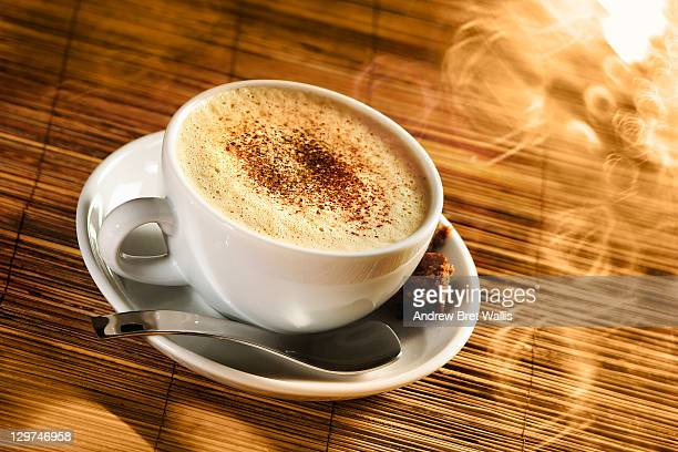 Fresh cappuccino with steam in sunlight
