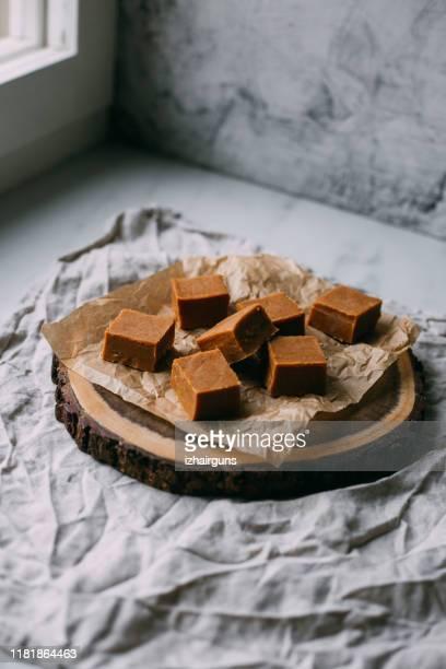 doces frescos do fudge do caramelo em uma placa de madeira com espaço da cópia no fundo de mármore - fudge - fotografias e filmes do acervo