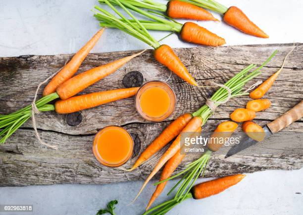fresh carrot juice  and raw organic vegetables over rustic wooden table - carrot stock pictures, royalty-free photos & images