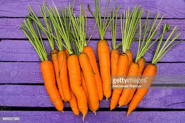 Fresh carrots on purple wooden table