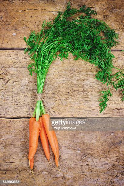 Fresh carrots with green leaves over wooden background