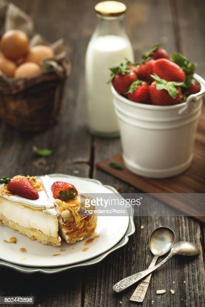 Fresh cheesecake with roasted almonds and strawberry on wooden table.