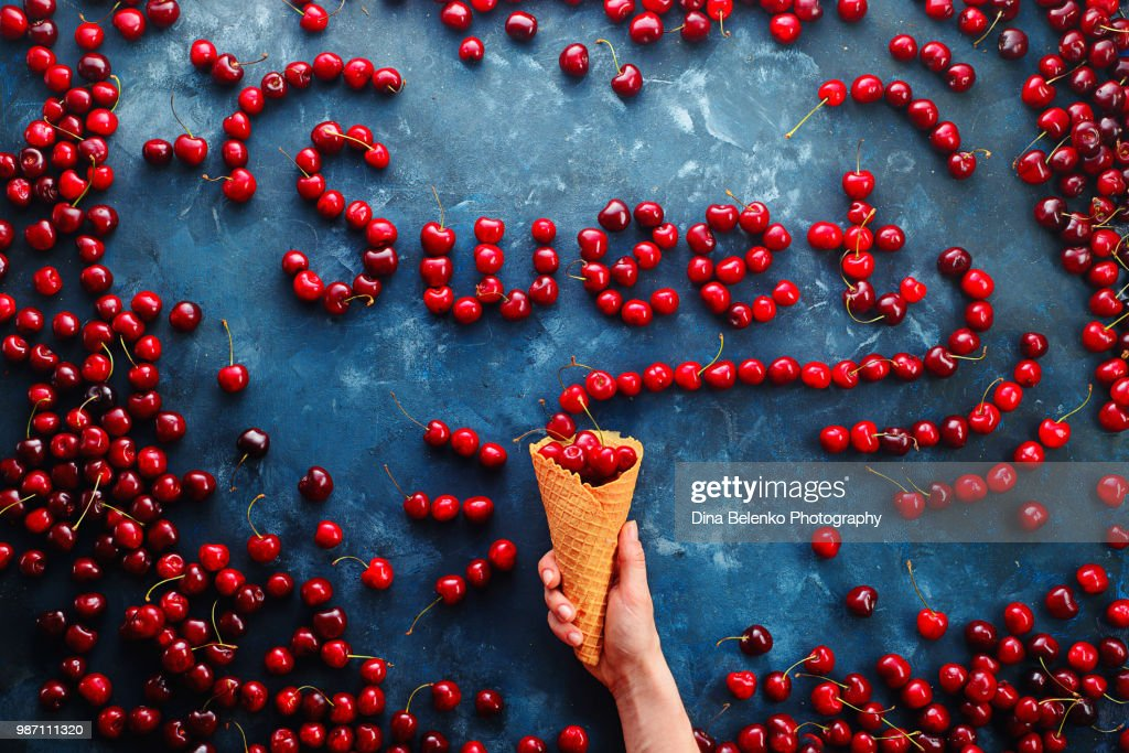 Fresh cherries in a waffle ice cream cone forming a word Sweet on a stone background with copy space. Food typography or food lettering concept with ripe berries : Stock Photo
