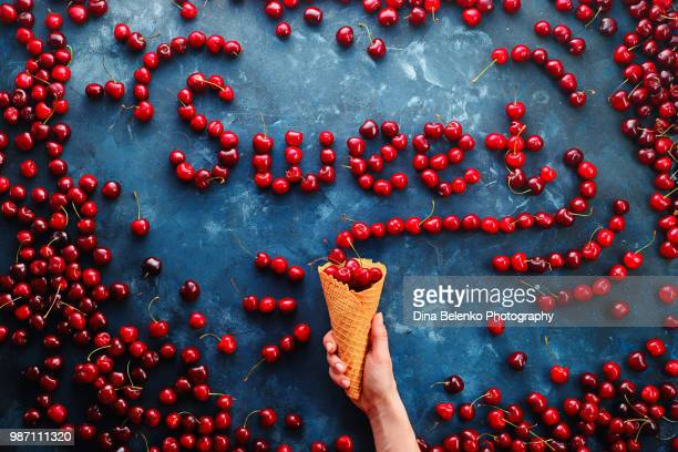 fresh cherries in a waffle ice cream cone forming a word sweet on a stone background with copy space. food typography or food lettering concept with ripe berries - font photos et images de collection