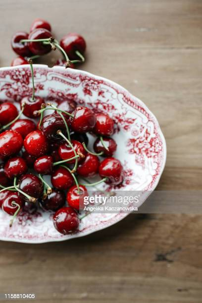 fresh cherries on a plate on a wooden table - サワーチェリー ストックフォトと画像