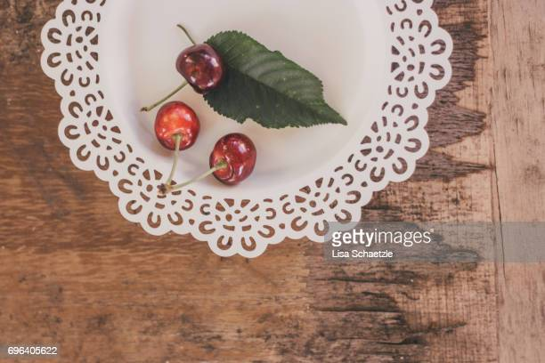 fresh cherries on a plate - gesunder lebensstil stock pictures, royalty-free photos & images