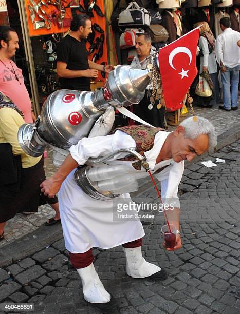 Fresh cherry juice vendor in street bazaar . Other keywords: man, merchant, metal tank, fresh fruit juice, cup, pouring, Turkish flag, market,...
