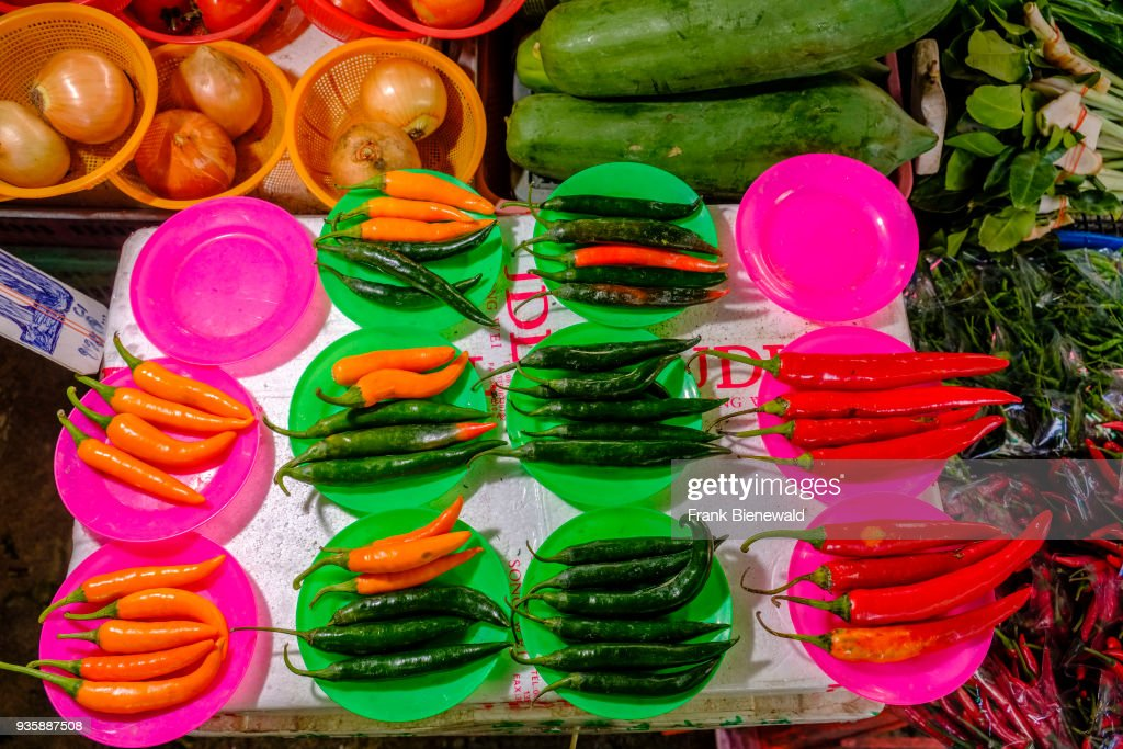 Fresh chillis arranged on colorful plastic plates are for sale at Nonthaburi Market. & Fresh chillis arranged on colorful plastic plates are for ...