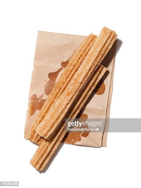Fresh churros on paper bag, view from above, studio shot