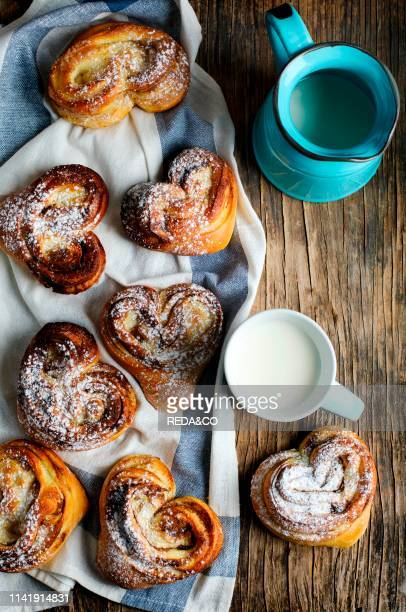 Fresh cinnamon buns and cup of milk top view