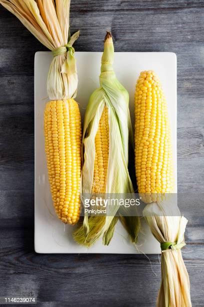 färsk majs med gröna blad stilleben grönsaker, söt gul majs, majs på trä bord, färsk majs - corn on the cob bildbanksfoton och bilder