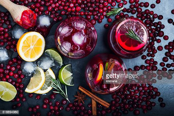Fresh cranberry juice cocktail, ripe cranberries and muddle stick on grey background viewed from above