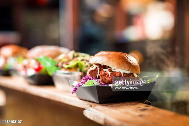 fresh crispy pork burgers in a row at food market - box container stock pictures, royalty-free photos & images