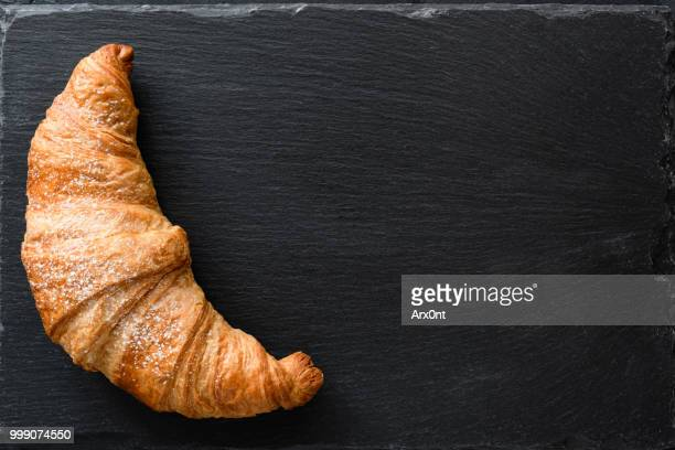 fresh croissant on black slate background - croissant stock pictures, royalty-free photos & images