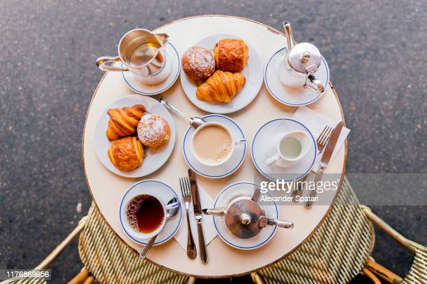 fresh croissants, coffee and tea in french cafe, paris, france - thee warme drank stockfoto's en -beelden