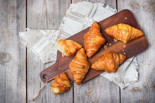Fresh croissants for breakfast on cutting board rustic table 607926954
