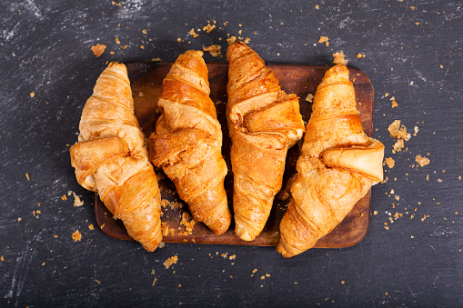 fresh croissants on a wooden board 854036652