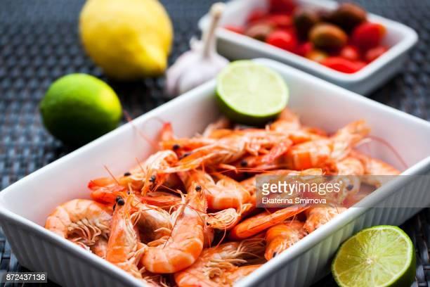 fresh delicious prawns with lime on the plate - pescado y mariscos fotografías e imágenes de stock