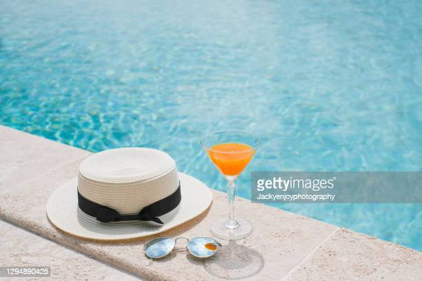 fresh drink an orange juice, hat and glasses on the floor in front of pool in background in koh samui. summer concept - swimming pool stock pictures, royalty-free photos & images