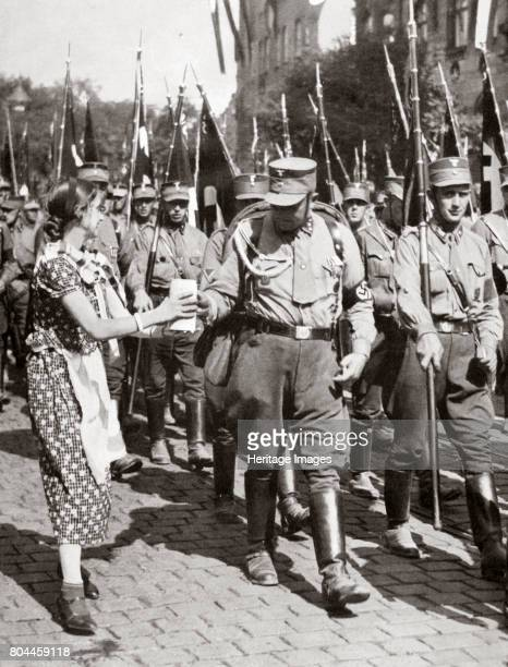 A Fresh Drink from a Tender Hand Tastes Twice as Good' c1933 A woman offers a drink to members of the SA marching in a parade Founded in c1919 the...