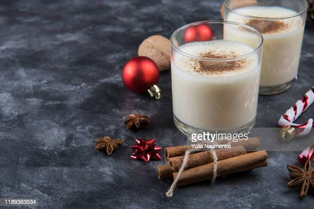fresh eggnog with cinnamon with christmas decorations on dark background. copy space, low key. - eggnog stock photos and pictures