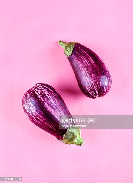 fresh eggplants on a pink background - eggplant stock pictures, royalty-free photos & images