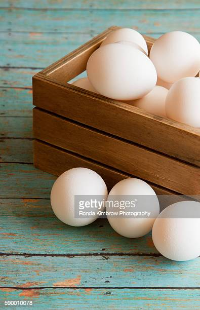 Fresh Eggs in a wooden crate on a wood plank board background