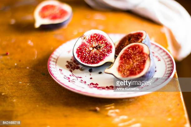 Fresh fig fruit on a dessert plate on a wooden table, selective focus
