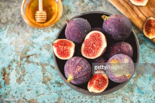 fresh figs and honey on rustic background - fig stock pictures, royalty-free photos & images