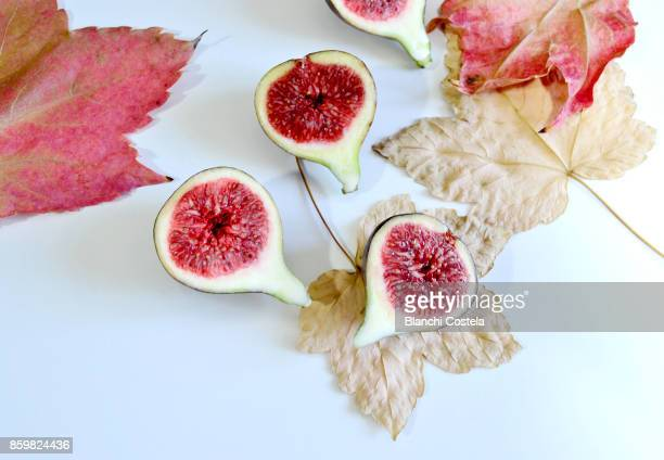 Fresh figs cut in half on a white table