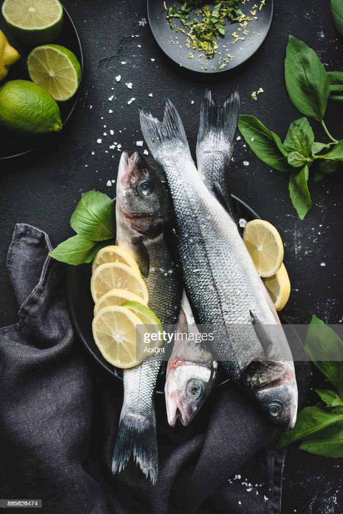 Fresh fish with lemon, spices and herbs ready for cooking on dark background : Stock Photo