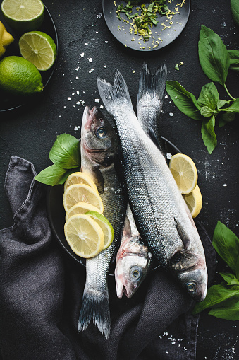 Fresh fish with lemon, spices and herbs ready for cooking on dark background - gettyimageskorea
