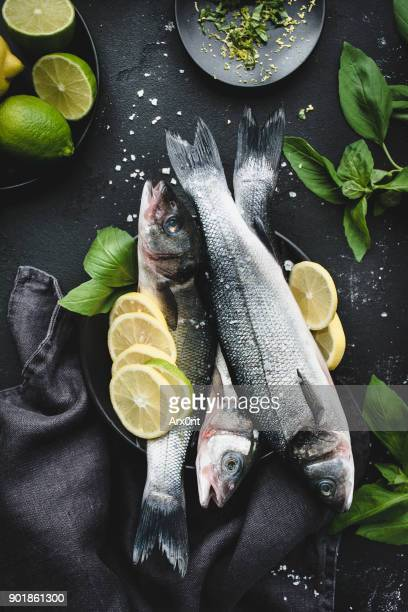 fresh fish with lemon, spices and herbs ready for cooking on dark background - dorado fish stock photos and pictures