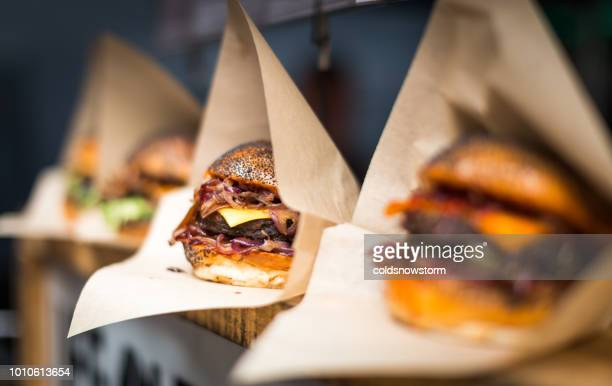 Fresh flame grilled burgers displayed in a row at food market