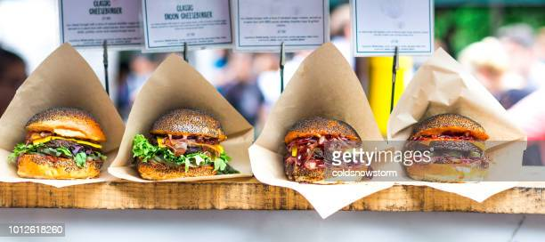 fresh flame grilled burgers displayed in a row at food market - street food stock photos and pictures