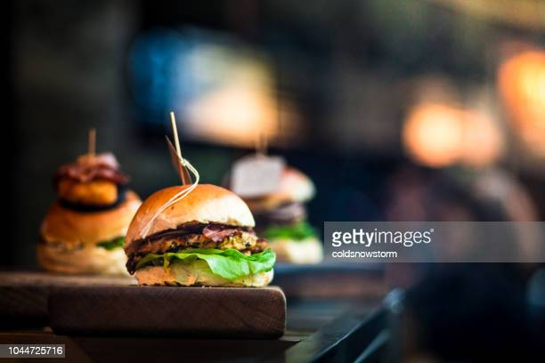 fresh flame grilled burgers displayed in a row at food market - burger stock pictures, royalty-free photos & images