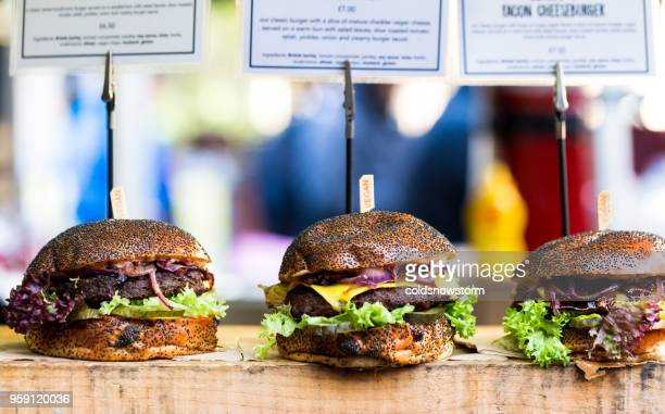 fresh flame grilled burgers displayed in a row at food market - borough market stock photos and pictures