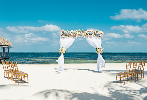 Fresh flower arbor on the beach with eight chairs for a small beach wedding - gettyimageskorea