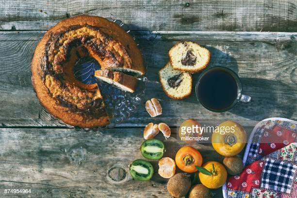 新鮮なフルーツ、コーヒー、木材の背景にケーキ