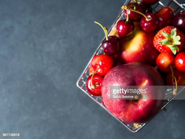 Fresh fruit in supermarket cart on black. Top view