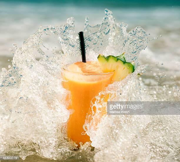 Fresh fruit juice on beach getting splashed