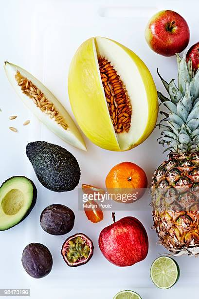fresh fruit overhead on white chopping board - tropical fruit stock pictures, royalty-free photos & images