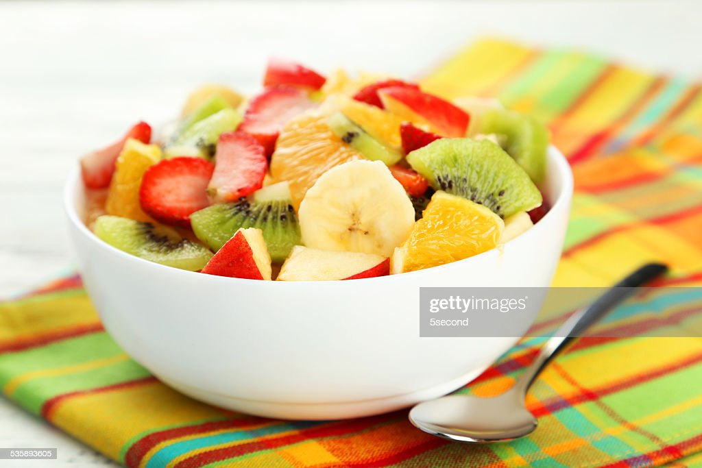 Fresh fruit salad on white wooden background : Stockfoto