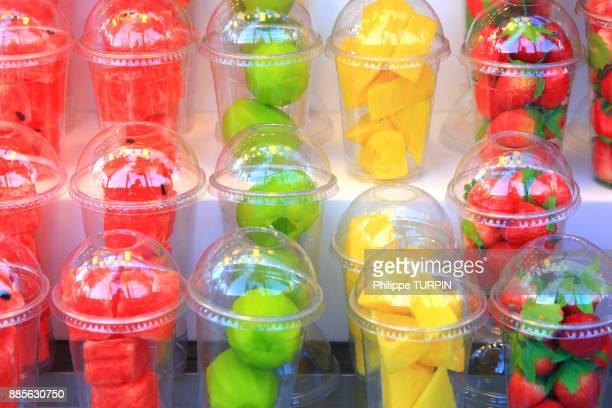 Fresh fruits in plastic glasses.