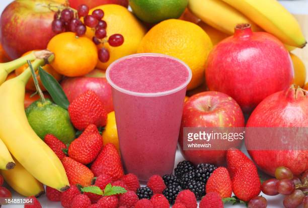 Fresh fruits surrounding a berry smoothie
